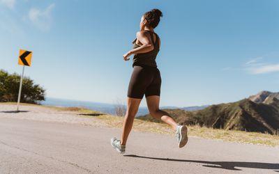 woman running on a coastal road