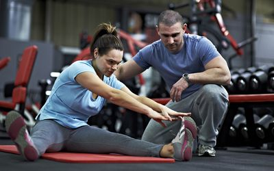 Healthy Female Stretching in Gym Before Workout