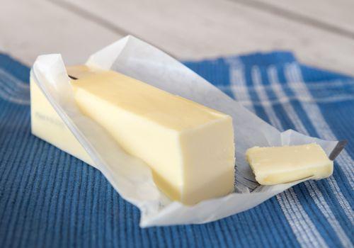Barra de mantequilla con el paquete abierto sobre un mantel