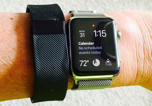 Fitbit Charge y Apple Watch en la muñeca