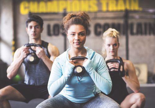 Mujer joven segura con compañeros de entrenamiento levantando pesas rusas en el gimnasio