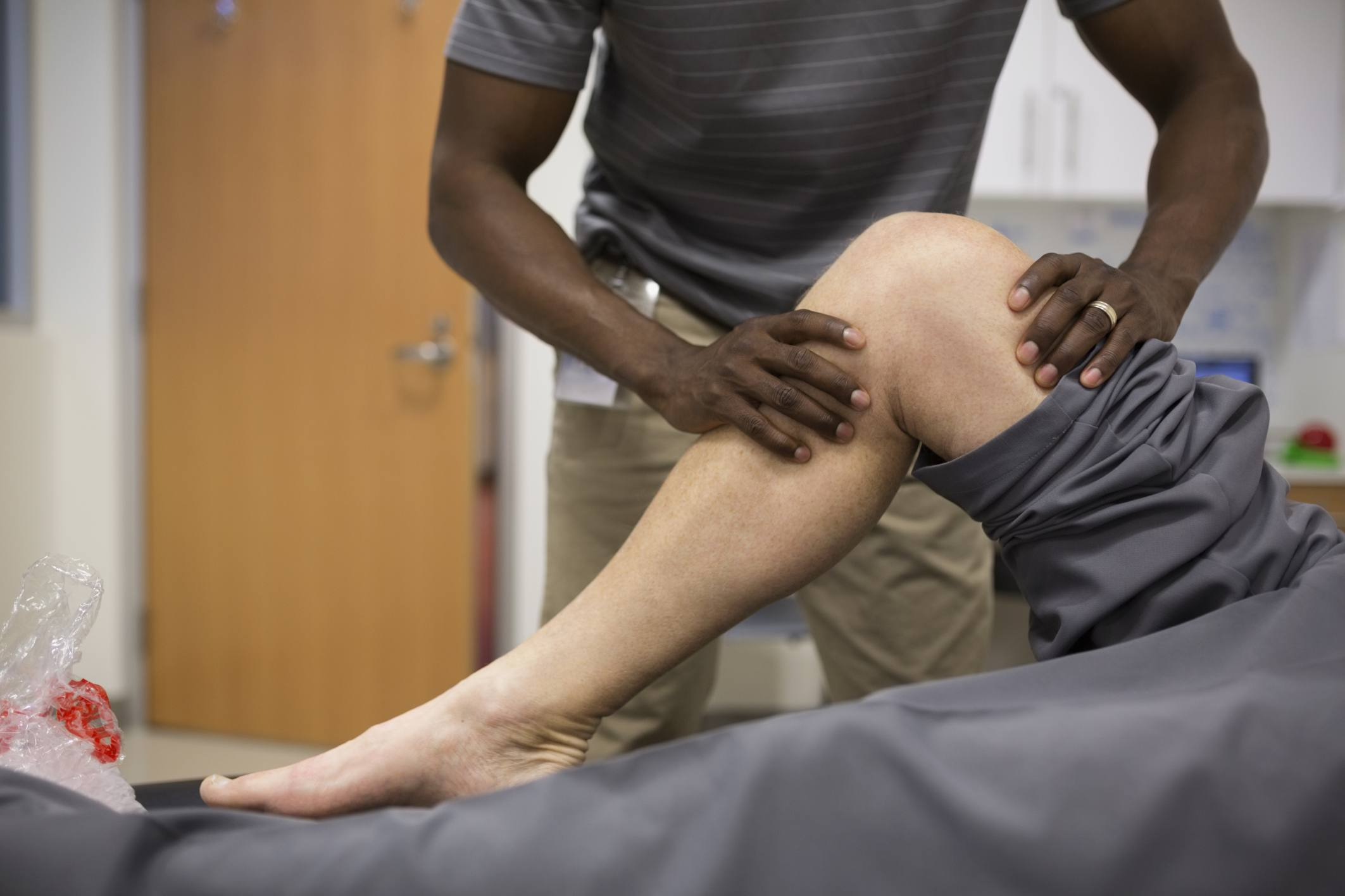 Man's knee being evaluated by a physical therapist