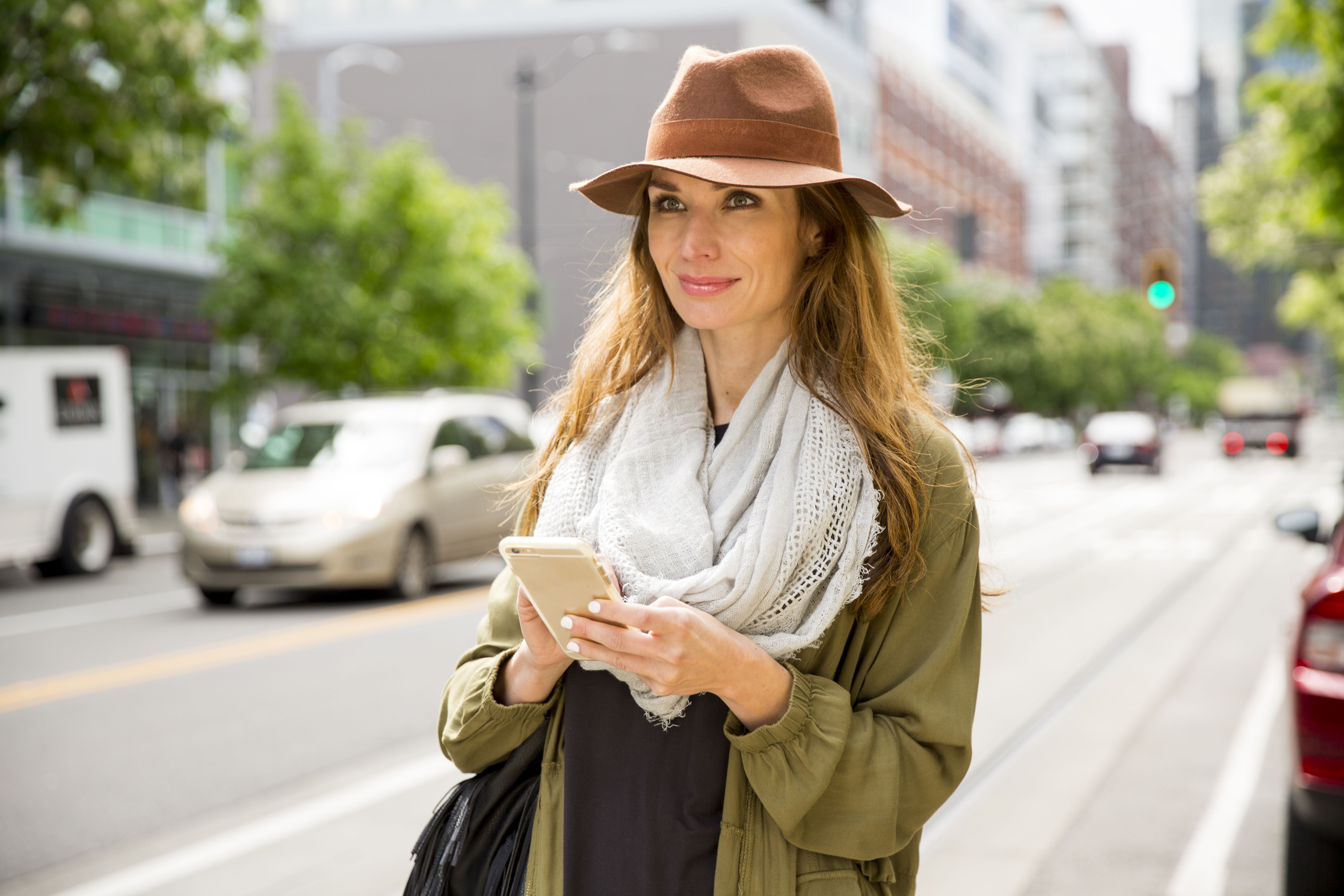 A female wearing a hat, using her smartphone on th street