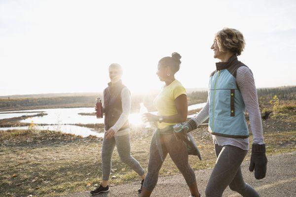 Women walking exercising on sunny path in autumn park