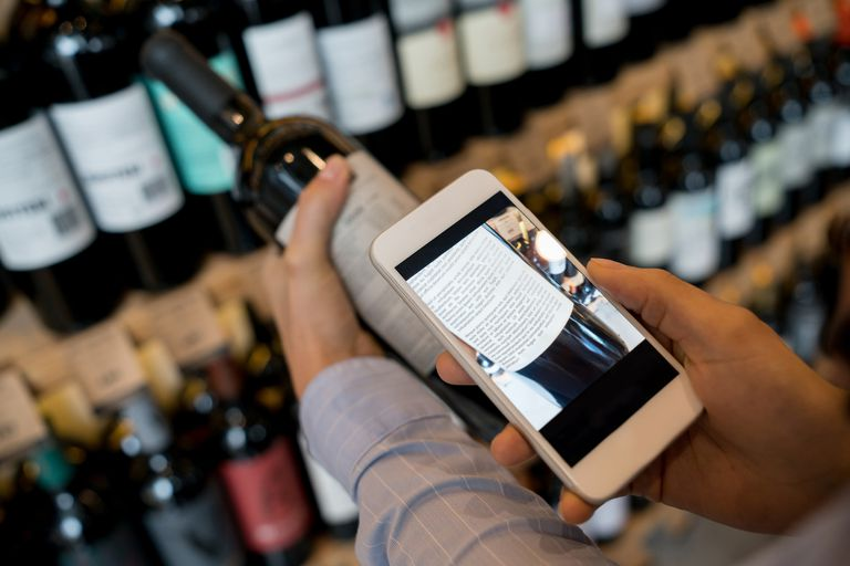 Unrecognizable woman using an application on smartphone to read more about the wine