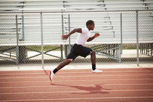 Black athlete doing shuttle runs on track