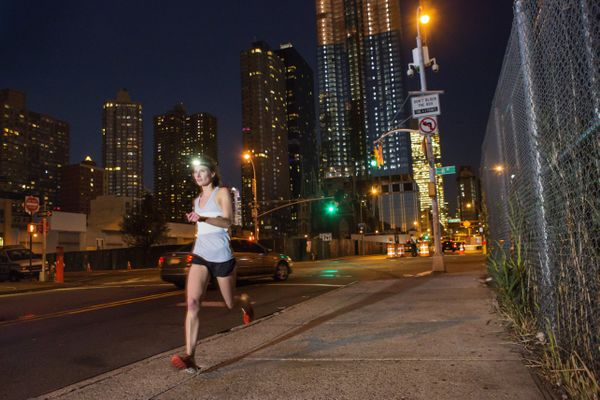 Runner at night with city in background