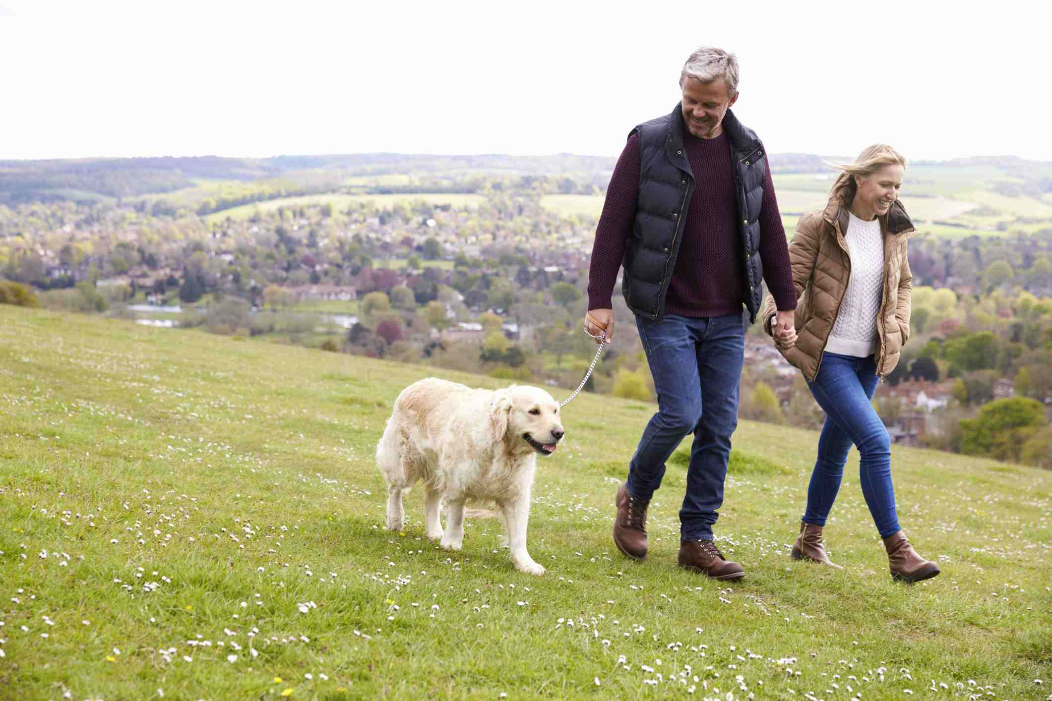 mature couple walking with dog