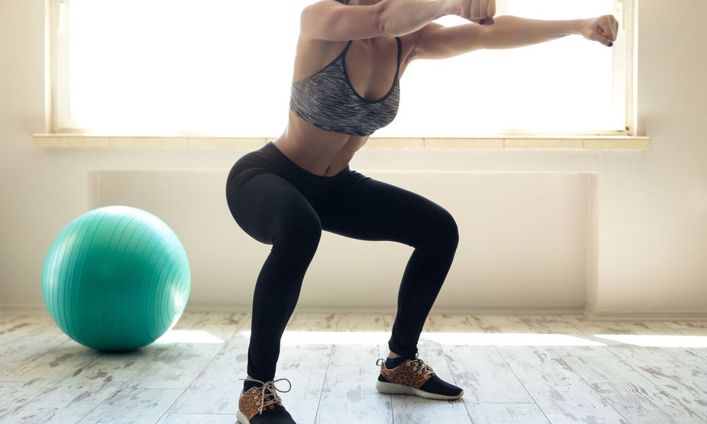 Woman in sportswear doing squat