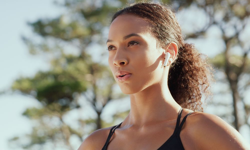 BIPOC woman wearing headphones during her fitness workout routine