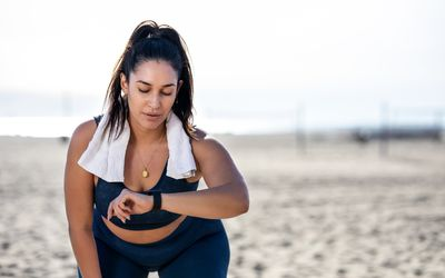 woman checking fitness watch while working out on beach