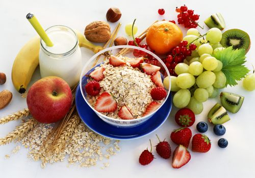 healthy breakfast foods, including fruit and oatmeal, on a white tabletop