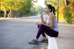 Woman runner resting on a curb