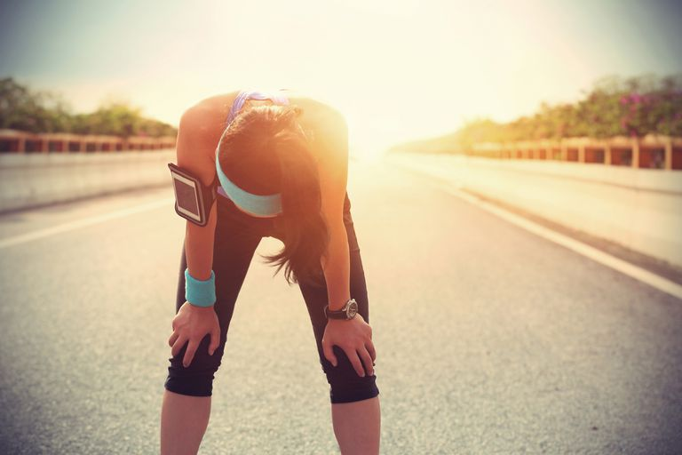 Woman bending over due to heat exhaustion while exercising outdoors