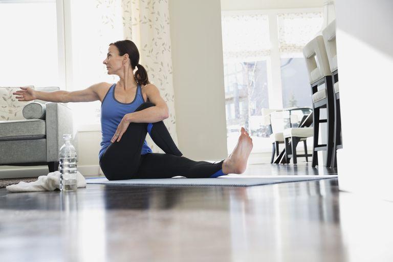 Mature woman doing yoga on mat
