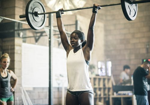 A young woman holds a barbell overhead in a CrossFit Gym.