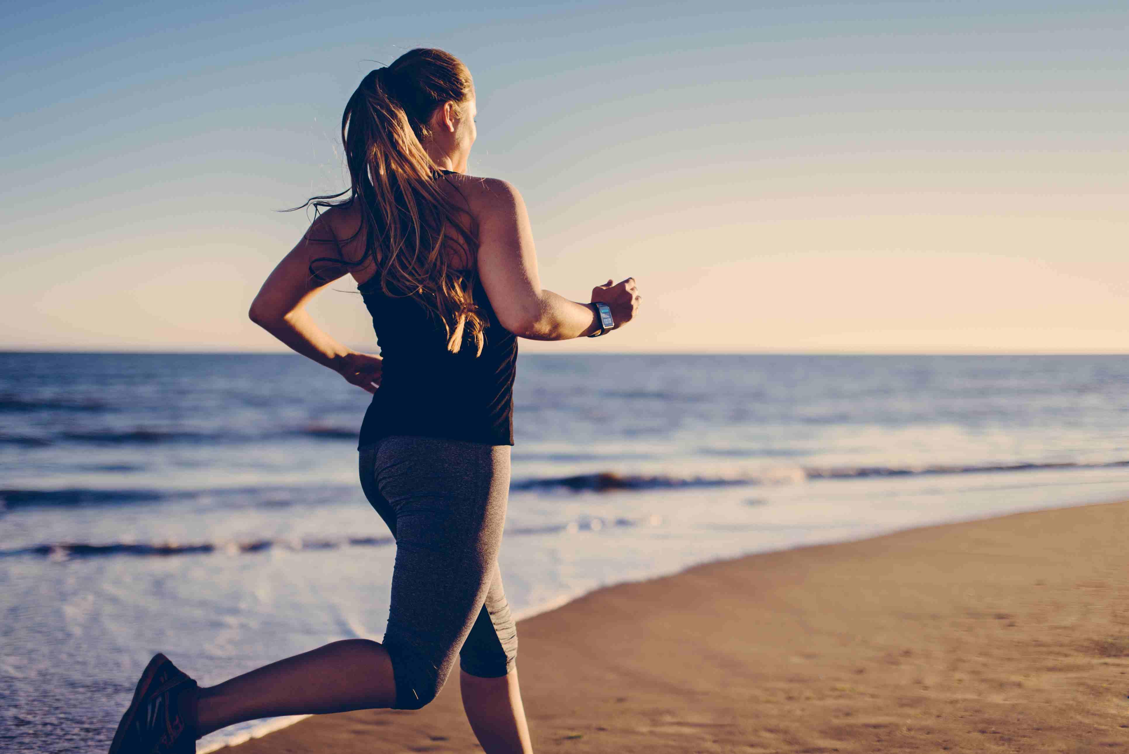 Mujer corriendo en la playa con reloj inteligente.