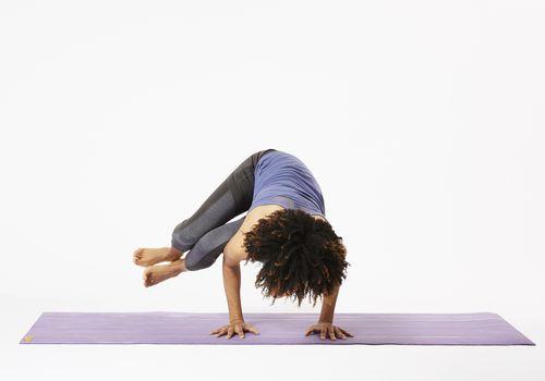 Mujer en estera de yoga en pose de cuervo lateral