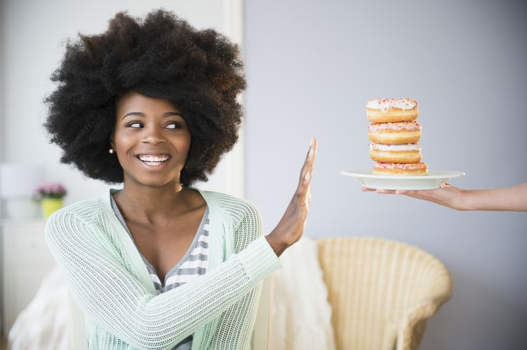 young black woman turning away a plate of donuts