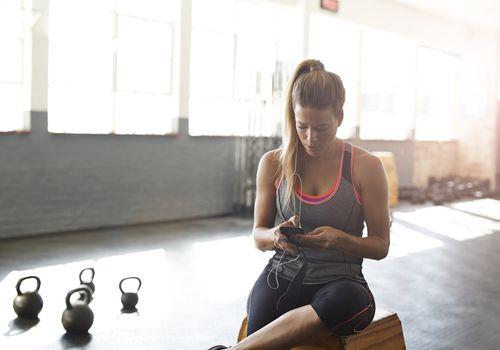 Mujer comprobando smartphone en el gimnasio
