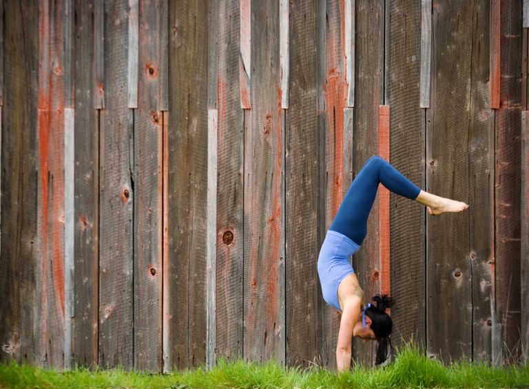Woman doing inverted yoga pose outside