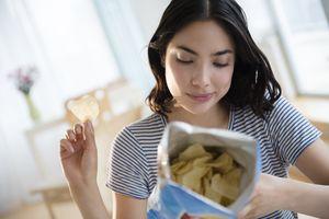 Woman looking at potato chip bag