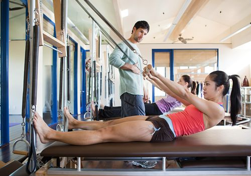 Dos mujeres con instructor de pilates