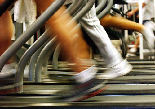 Piernas borrosas en cintas de correr en el gimnasio.