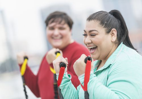 Mujer hispana, amiga haciendo ejercicio con bandas de resistencia