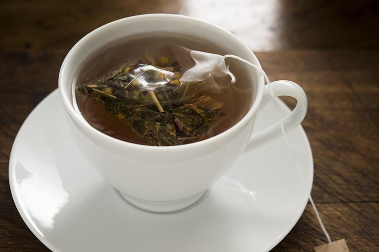 A cup of camomile tea with a full leaf herbal tea bag.