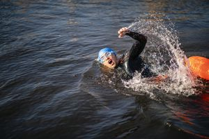 A young man wearing a swim cap and goggles wild swimming in Derwent Water in The Lake District in Cumbria