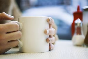 close up of hands holding cup of coffee in cafe