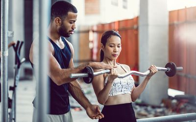 woman doing barbell curls under supervision of personal trainer
