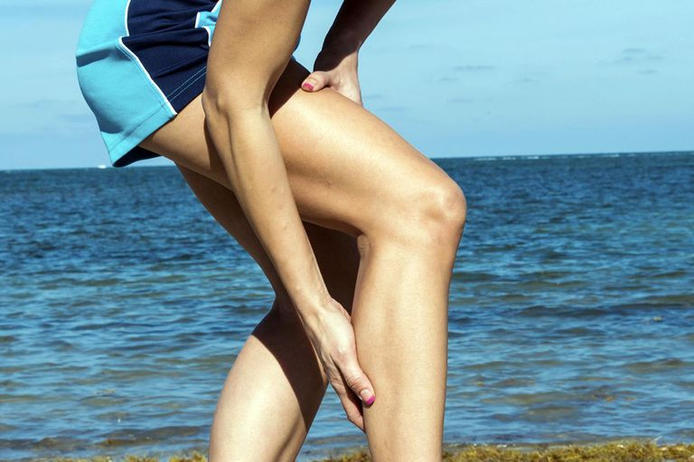 Hispanic Female jogger, having a cramp in her calf.