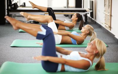 Women doing Pilates exercises. The focus is on the woman in the middle.