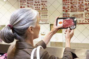 Mature woman checking package of meat, rear view, close-up