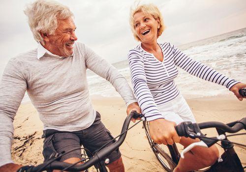 Pareja senior activa andar en bicicleta en la playa