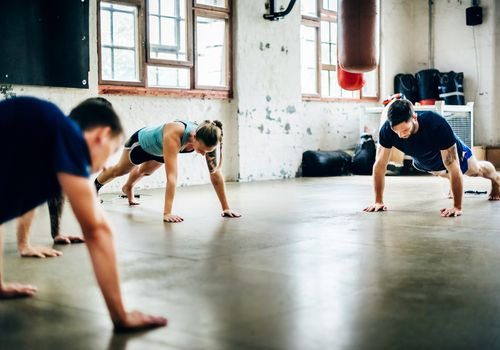 Three CrossFit athletes performing push-ups in a CrossFit gym.