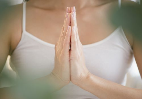 Mixed race woman meditating with clasped hands