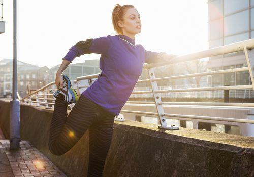 Corredor femenino estirando la pierna en el espacio urbano