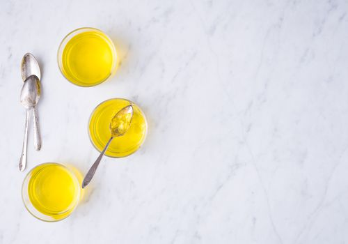 Jello in cups with metal spoons on a countertop.