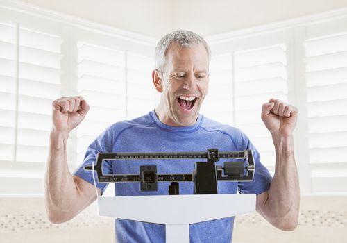 Hombre maduro sonriendo mientras se pesa en la báscula