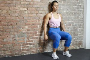 Woman doing a wall sit against a brick wall in gym