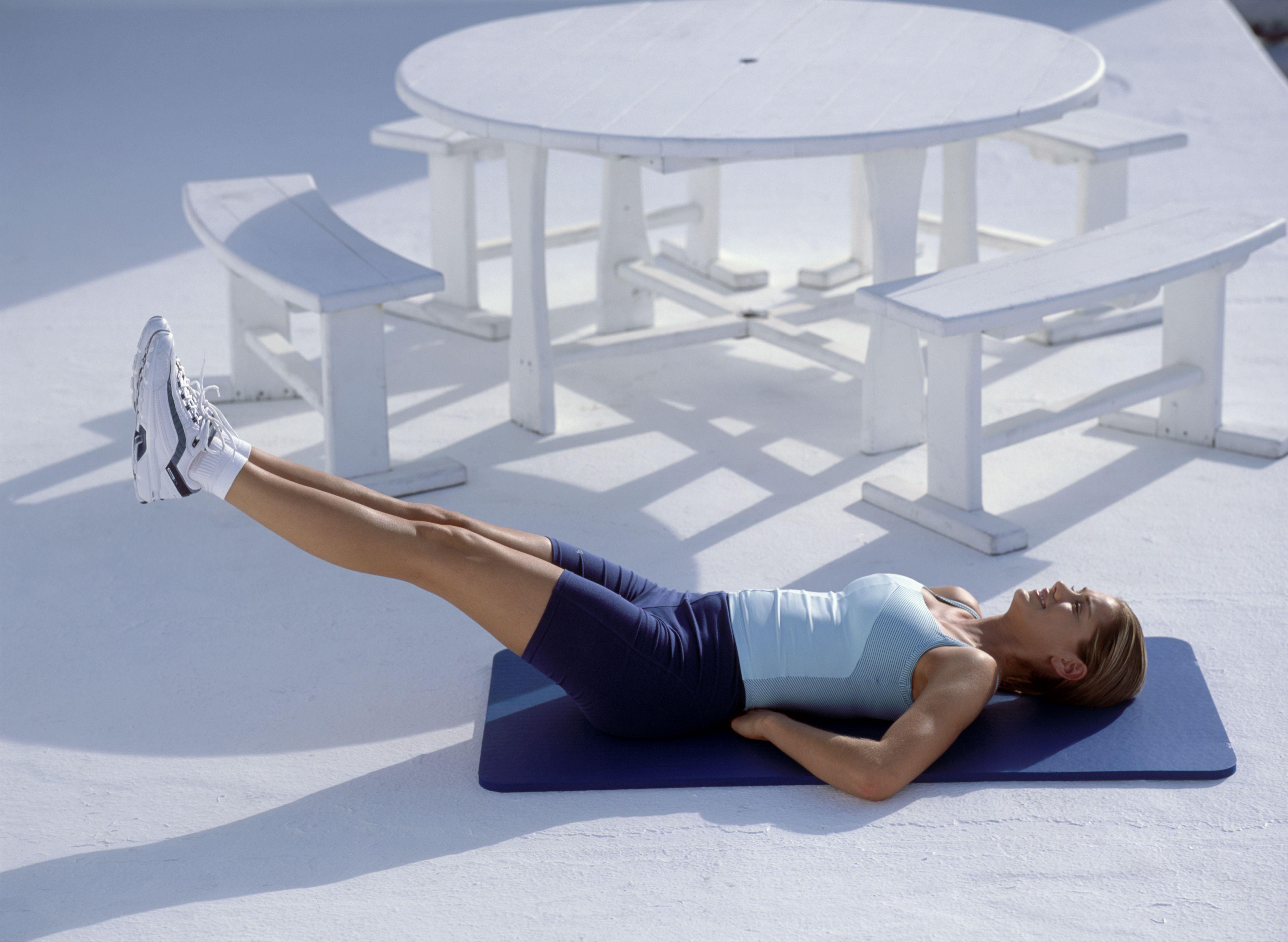 Mujer haciendo ejercicio de yoga, acostada sobre su espalda, piernas levantadas en el aire