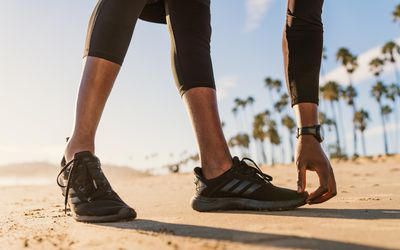 runner stretching on beach and touching toes
