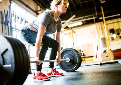 mujer preparándose para hacer un peso muerto