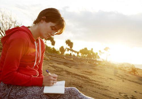 Mujer joven escribiendo en diario en la playa