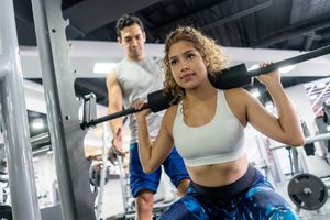 determined young woman working out her legs and coach standing behind her at the gym