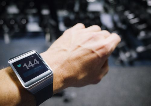woman's wrist showing heart rate on smartwatch