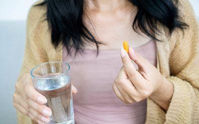 Woman taking a turmeric capsule